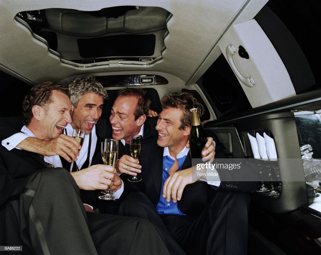 Four mature men drinking champagne in back of limousine, laughing