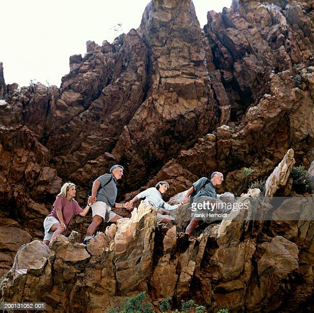 Four mature people walking hand in hand across rocks, low angle view