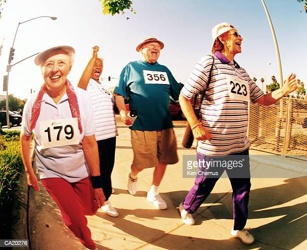 Four mature women walking down street, paper numbers pinned to tops