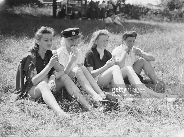 Four members of the Women's Auxiliary Air Force relax and eat ice creams while watching their colleagues competing in an RAF sports meeting 8th July...