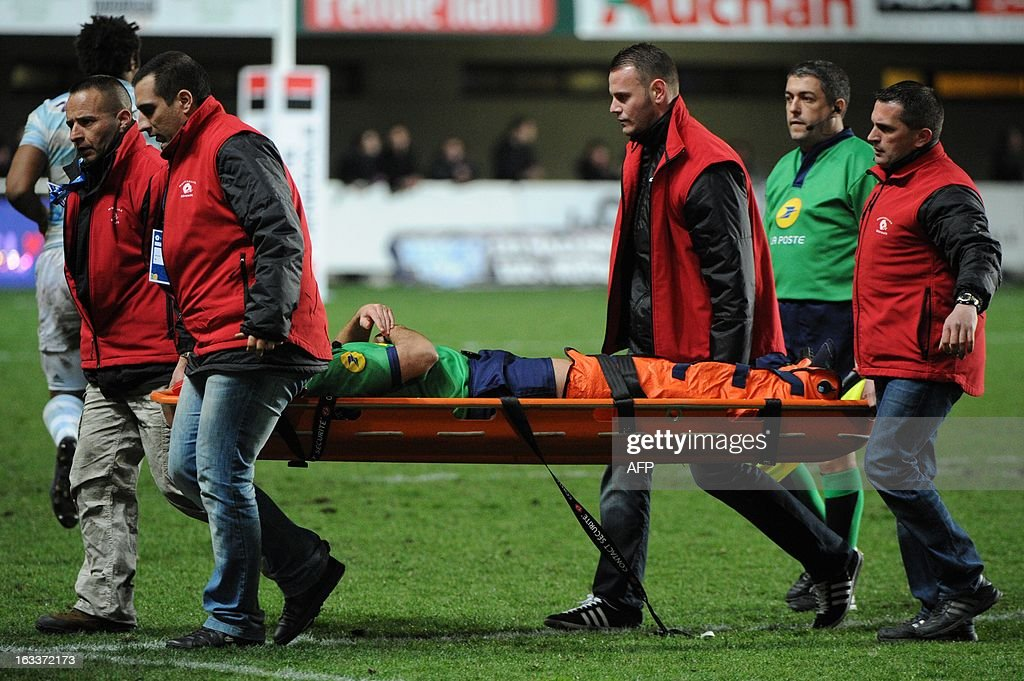 Four men carry referee Mathieu Raynal on a stretcher after he fell and injured himself seriously during the French Top 14 rugby Union match Montpellier vs Racing Metro on March 8, 2013 at the Yves du Manoir stadium in Montpellier, southwestern France.