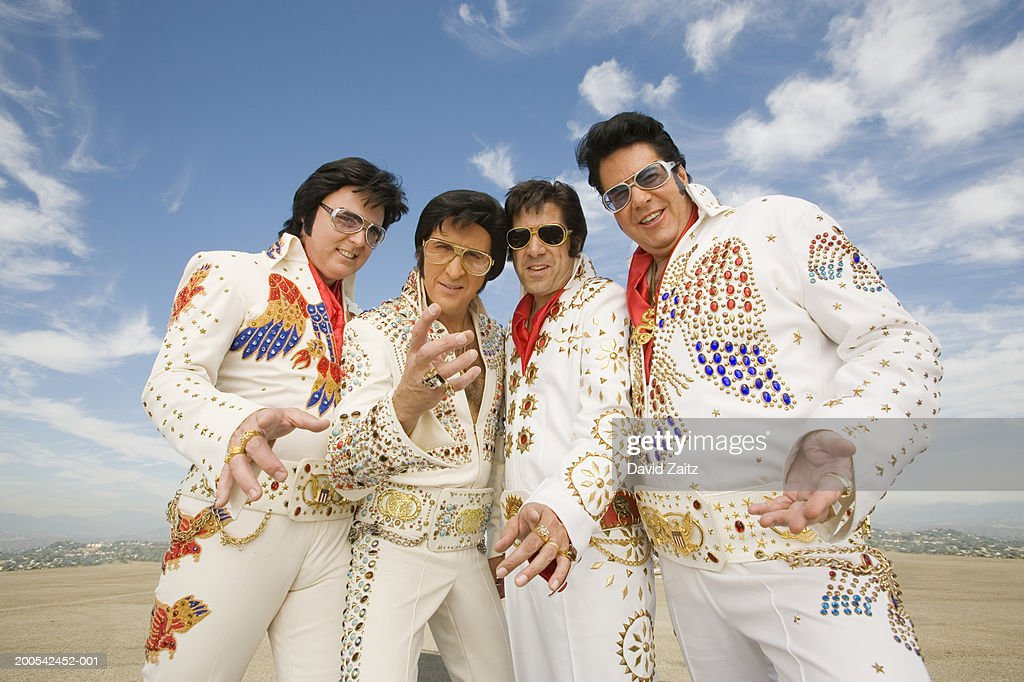 Four men dressed as Elvis Presley posing, gesturing, portrait