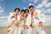 Four men dressed as Elvis Presley posing, gesturing, portrait