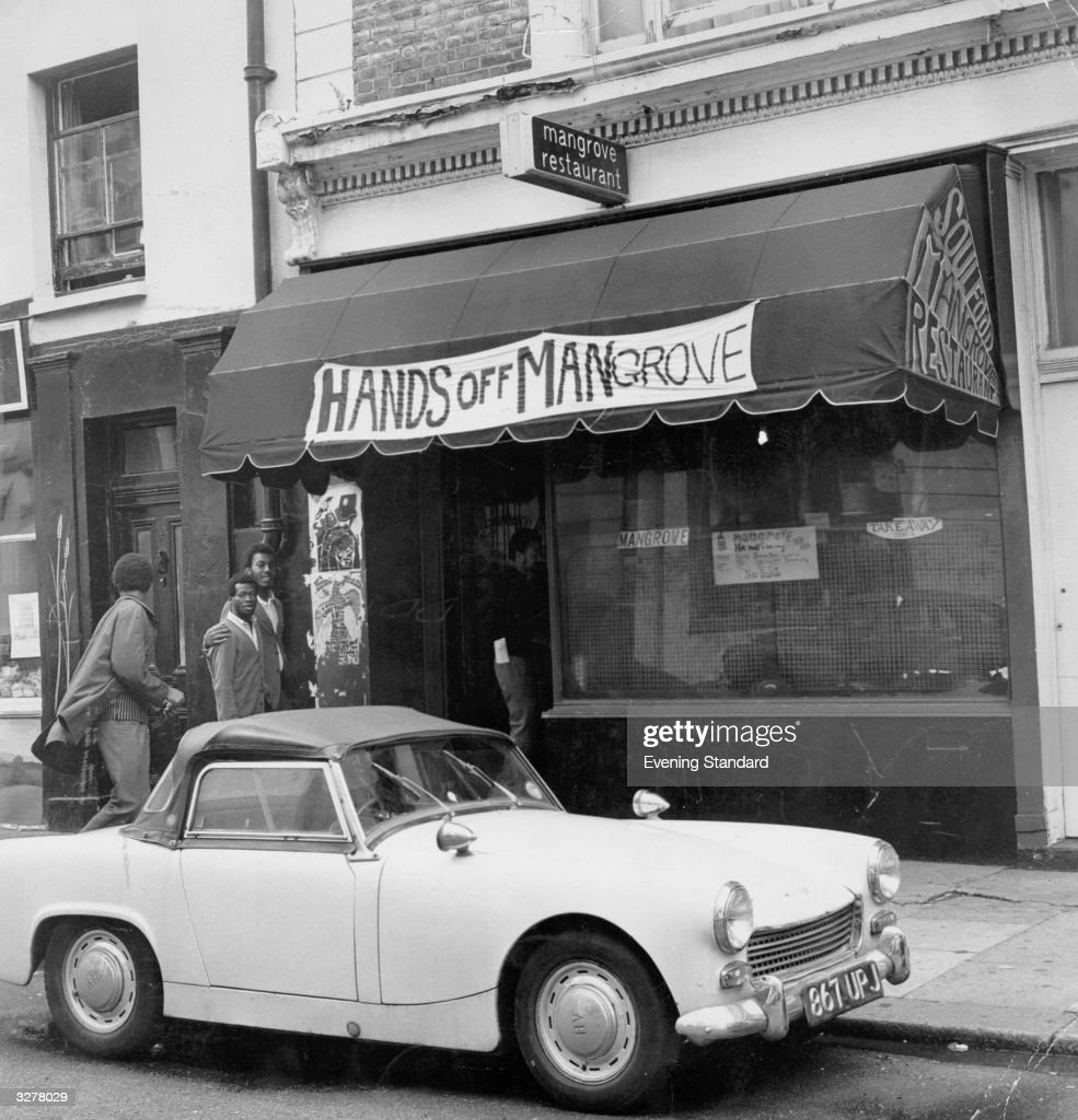 A view of West Indian immigrants standing outside the 'Hands Off Mangrove' restaurant in London.