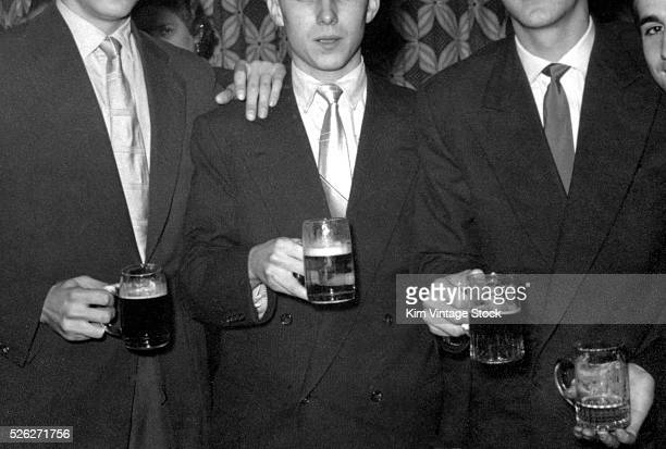 Four men hold mugs of beer ca 1955