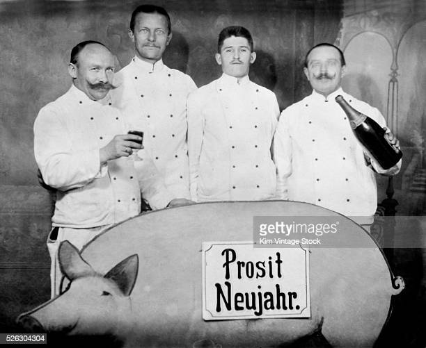 Four men in waiter outfits stand behind a card board pig and toast the New Year in Germany