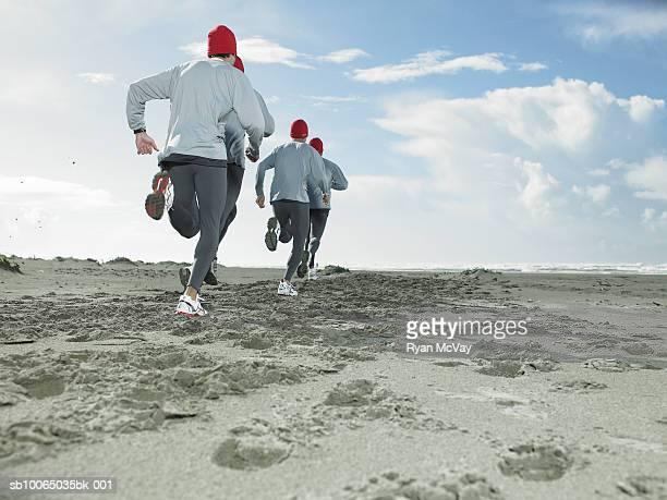 Four men jogging on beach, rear view