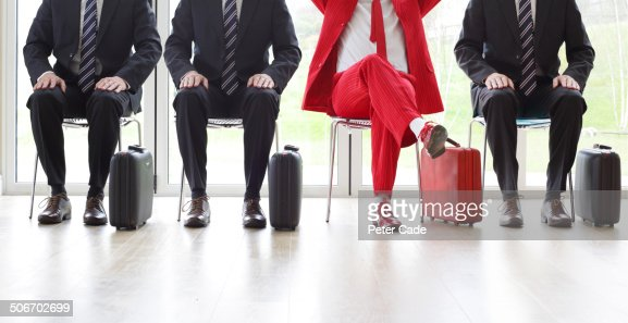Four men on chairs, three black one red suit