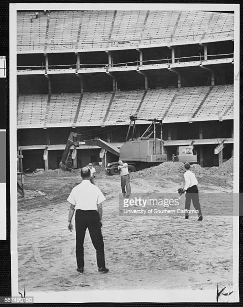 Four men playing baseball at the Dodgers Stadium construction site in Chavez Ravine Los Angeles