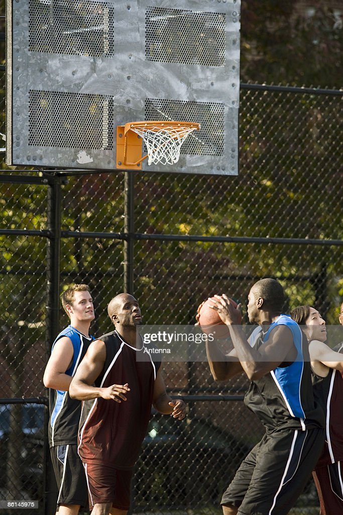 Four men playing basketball : Stock Photo