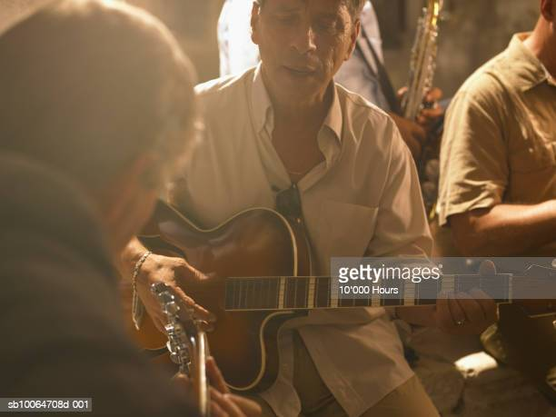 Four men playing instruments outdoors at sunset, close up
