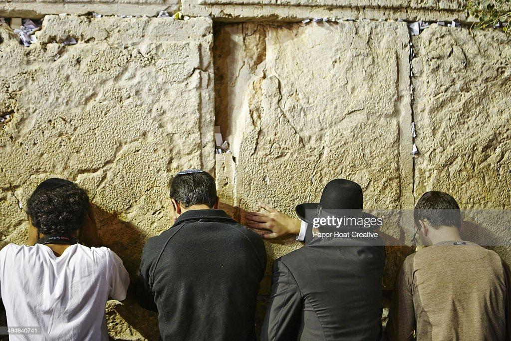 Four men praying by the Western Wall, Jerusalem : Stock Photo
