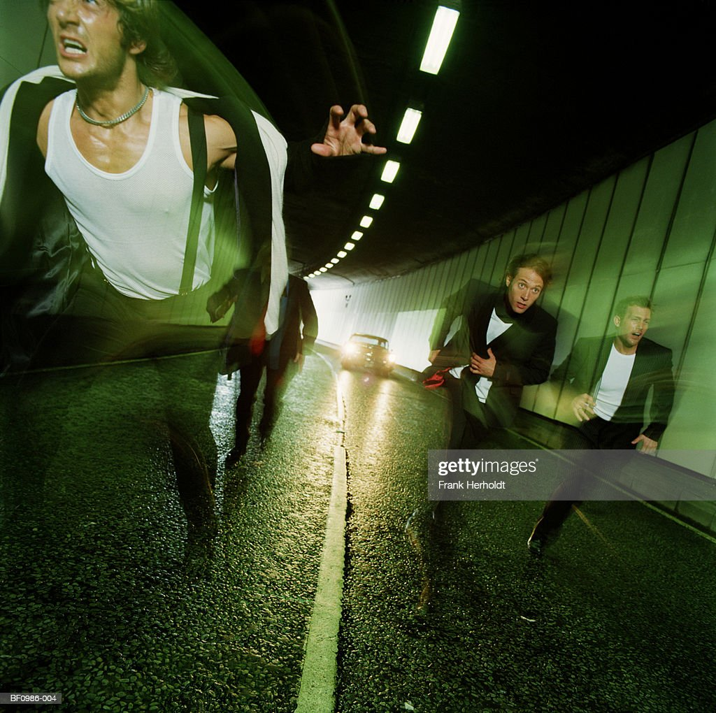 Four men running through tunnel, pursued by car (blurred motion)