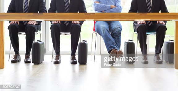 Four men sat at table, one in casual dress