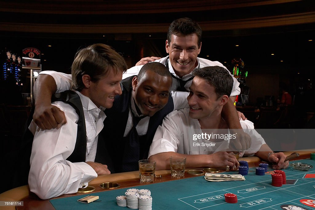 Four men sitting in casino playing roulette, smiling