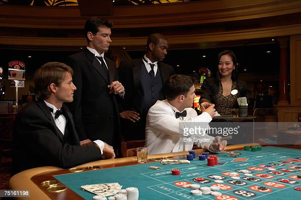 Four men sitting in casino playing roulette, waitress serving drinks