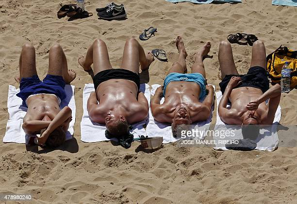 Four men sunbathe on a beach of the tourist village of Cascais on the outskirts of Lisbon on June 29 2015 Temperatures soared above 40 degrees across...