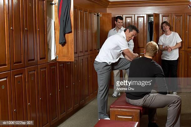 Four men talking in locker room
