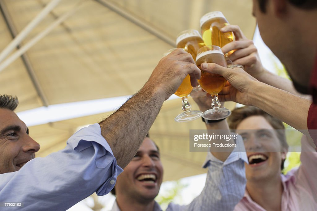 Four men toasting outdoors