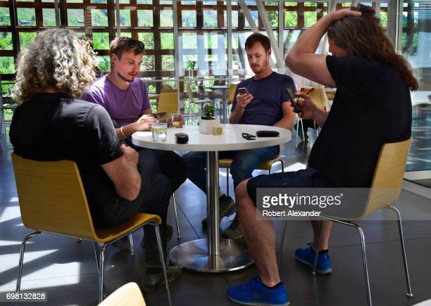 Four men use their smartphones or mobile devices as they sit around a table in a cafe in the Aspen Museum of Art in Aspen Colorado