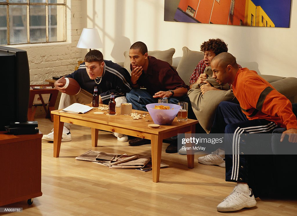 Four Men Watching a Football Game on Television : Stock Photo