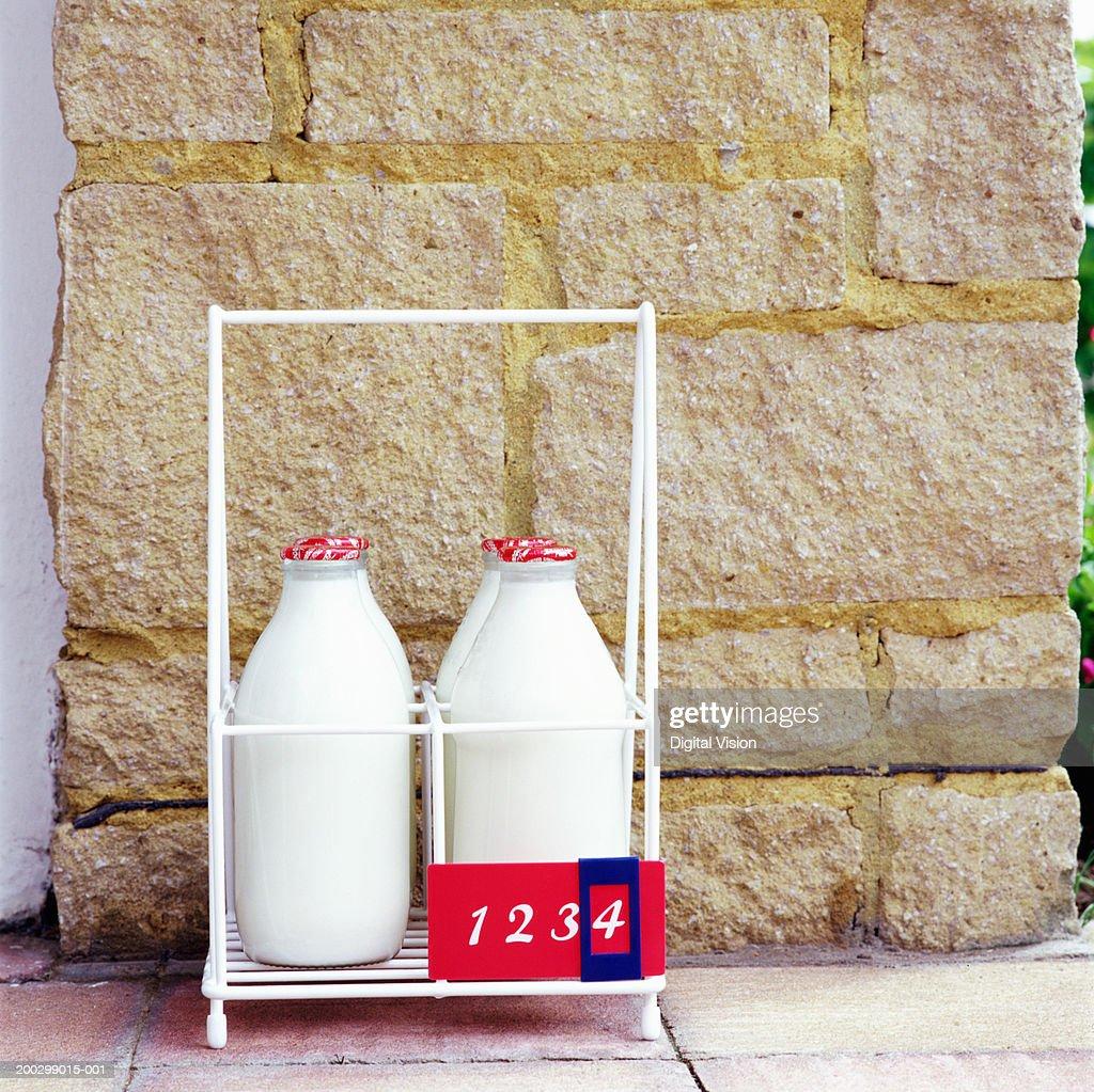 Four milk bottles in holder, close-up