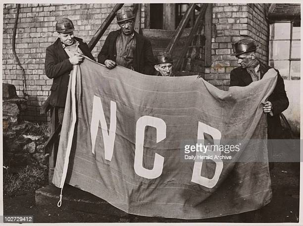 Four miners with the NCB flag 1946 A photograph of four miners from the Montague Pit near Newcastle holding the new National Coal Board flag taken by...