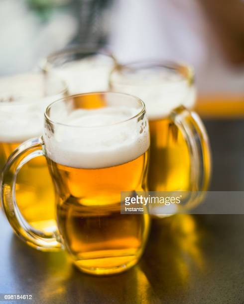 Four mugs of pilsner beer on a table, as shot in Prague.