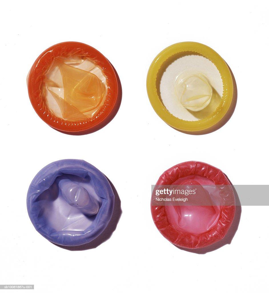 Four multicoloured condoms on white background, overhead view : Stock Photo