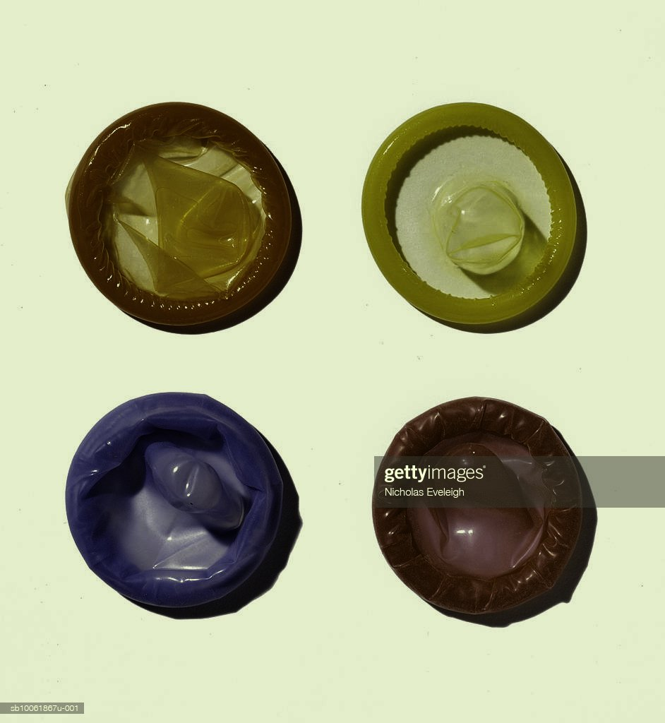 Four multicoloured condoms on white background, overhead view