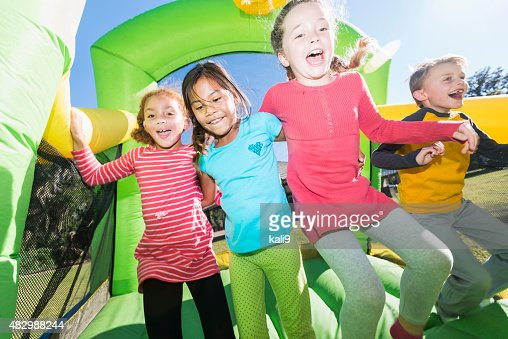 Four multi-ethnic children jumping on bouncy castle