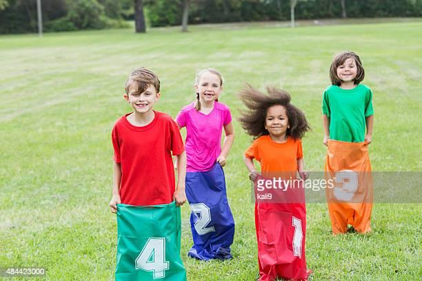 Four multiracial children in potato sack race
