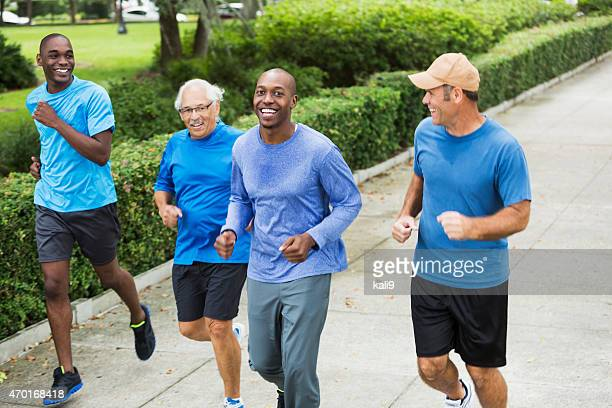 Four multiracial men jogging in park