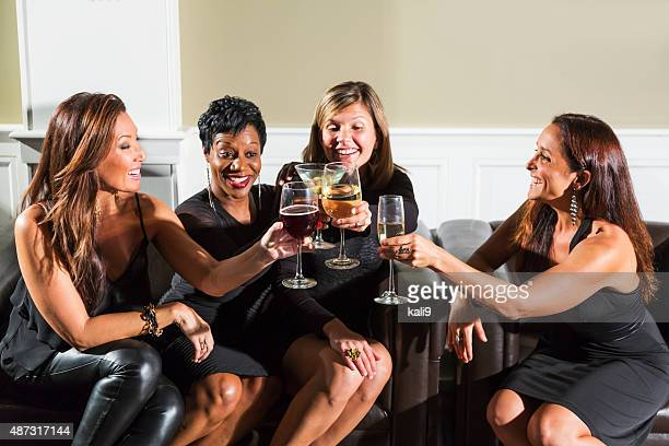Four multiracial women at party raising glasses to toast