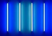 four neon tubes or lamps on the wall
