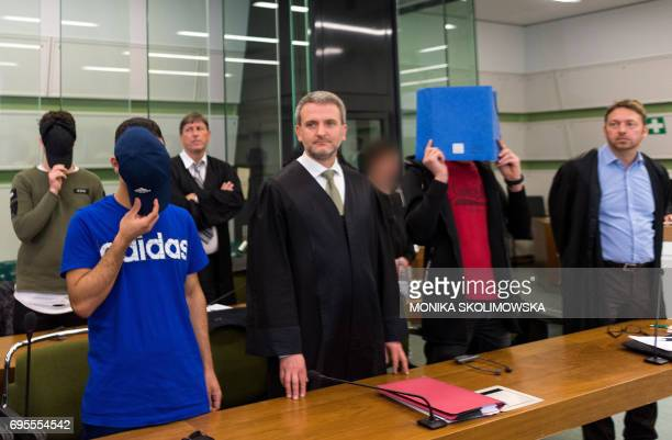 Four of six young men accused of setting fire to a sleeping homeless man stand next to their lawyers as they wait for their trial at court in Berlin...