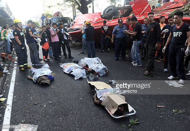 Four of the 22 bodies lay on the road beside the crashed bus that fell from an elevated highway in Manila on December 16 2013 Twentytwo people were...