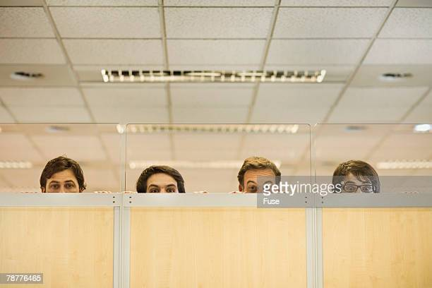 Four Office Workers Peering Over Partition
