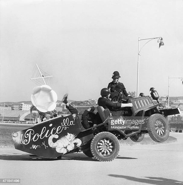 'Four officials of Civile Police performing a complicated exercise based on the presence of a offroad vehicle carrying a gramophone on its rear the...