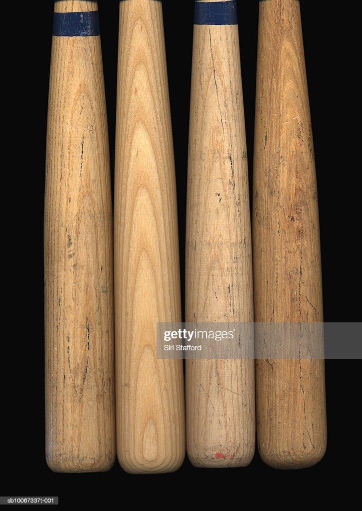 Four old baseball bats on black background