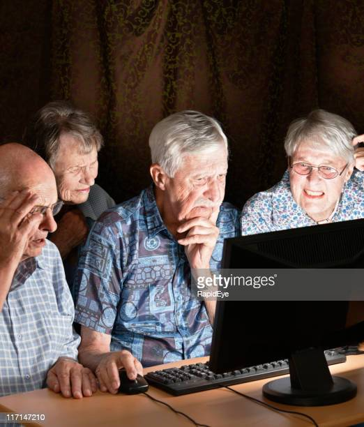 Four old people are fascinated by image on computer screen