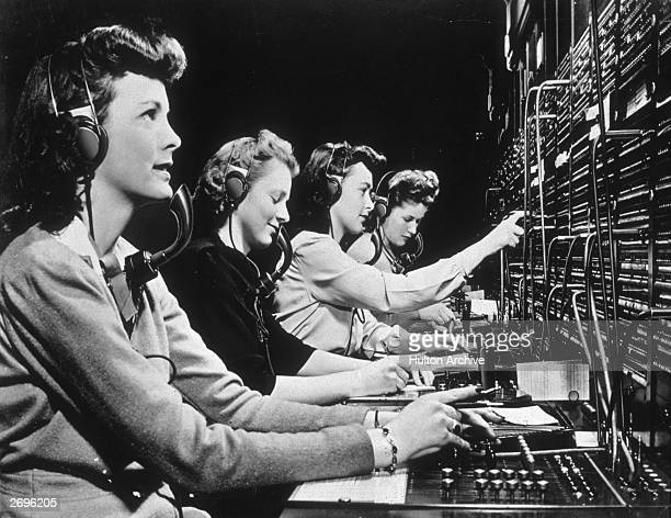 Four operators connect calls while working at a switchboard