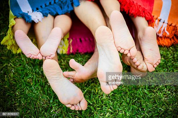 Four pairs of feet stick out the end of a colorful blanket on the grass