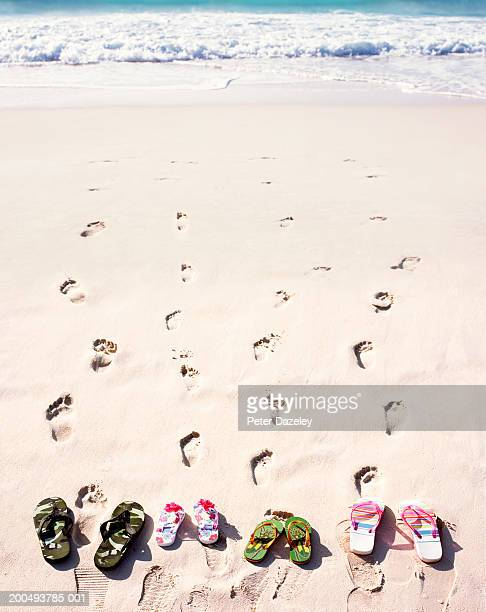 Four pairs of flip flops on beach, with footprints in sand