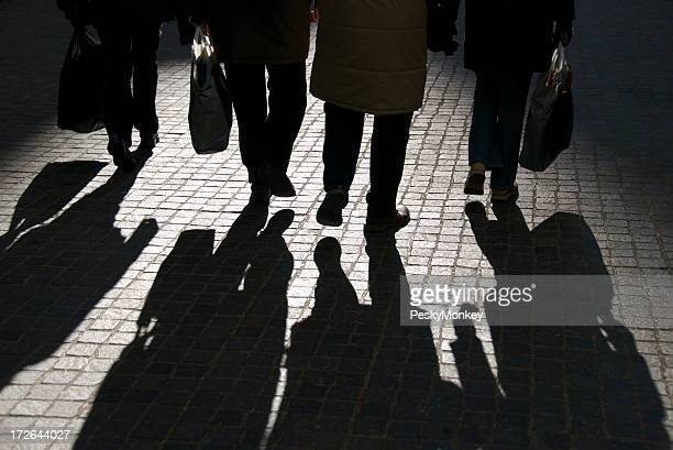 Four People and Shadows Walk Abreast