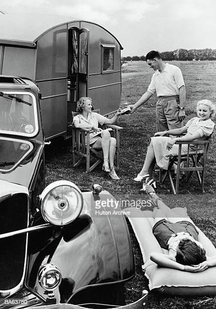 Four people at campsite with caravan and car (B&W)