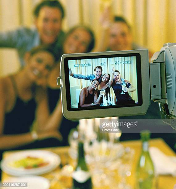 Four people at dinner party, view through camcorder screen