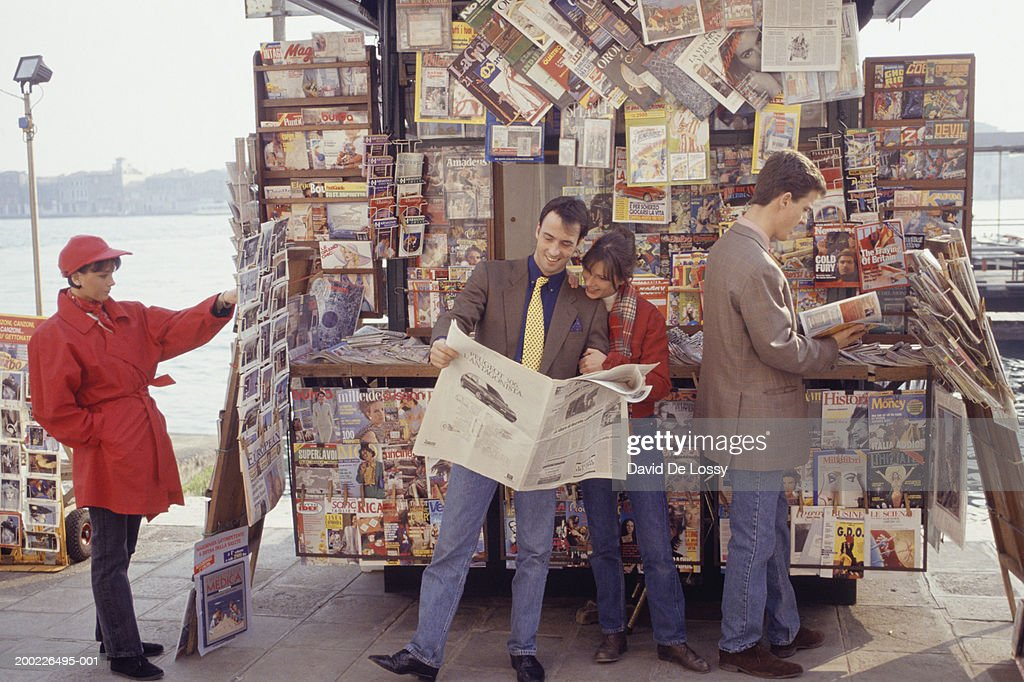 Four people at kiosk, couple reading newspaper : Stock Photo