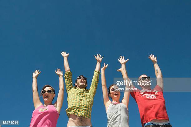 four people cheering celebrating hands in the air