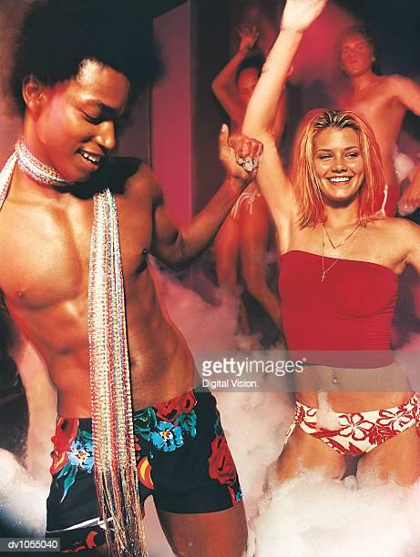 Four People Dancing in Soap Bubbles in a Nightclub